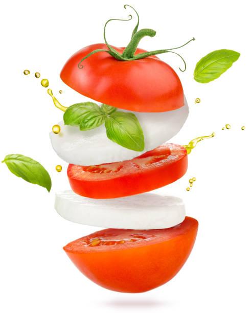 caprese-salat fliegen auf weißem hintergrund - caprese salat stock-fotos und bilder