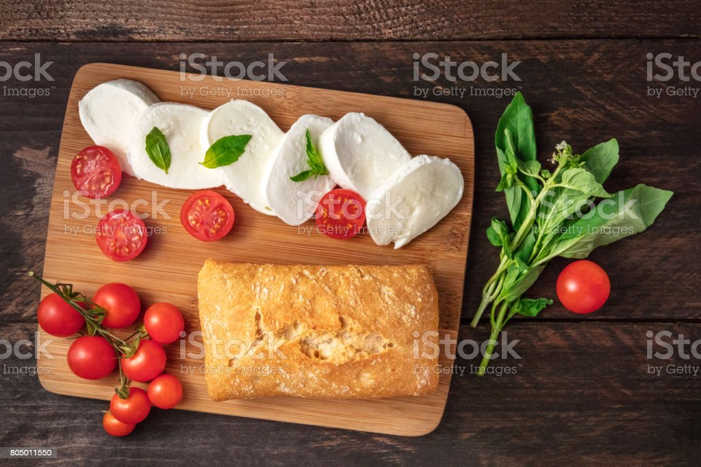 Caprese salad ingredients on rustic texture with copyspace stock photo