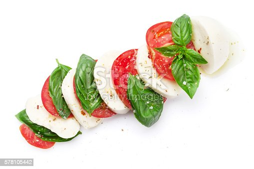 Caprese salad. Mozzarella cheese, tomatoes and basil herb leaves. Isolated on white background. Top view