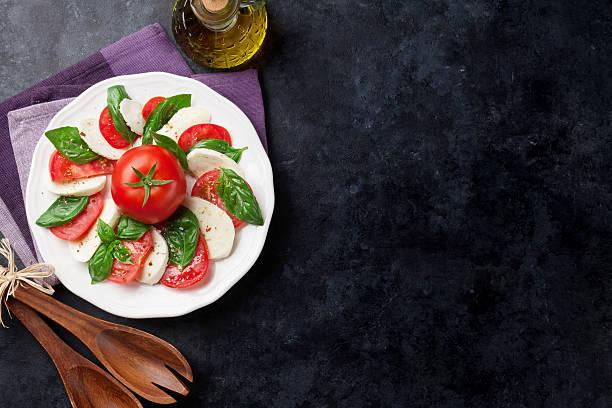 caprese salad. mozzarella, tomatoes and basil - caprese salat stock-fotos und bilder