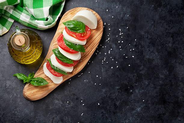 caprese-salat. mozzarella, tomaten und basilikum - caprese salat stock-fotos und bilder