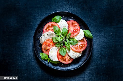 Top view of a caprese salad on a black plate. The salad is at the center of the image and is on a dark blackboard backdrop.  Low key DSLR photo taken with Canon EOS 6D Mark II and Canon EF 24-105 mm f/4L