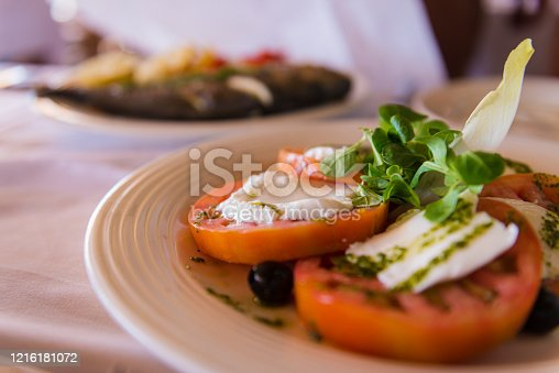 Close up of plate with caprese salad and olives