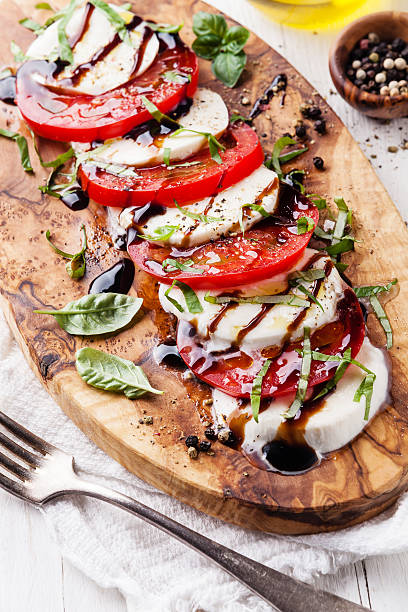 Caprese salad Caprese salad Tomato and mozzarella slices with basil leaves on olive wood cutting board balsamic vinegar stock pictures, royalty-free photos & images