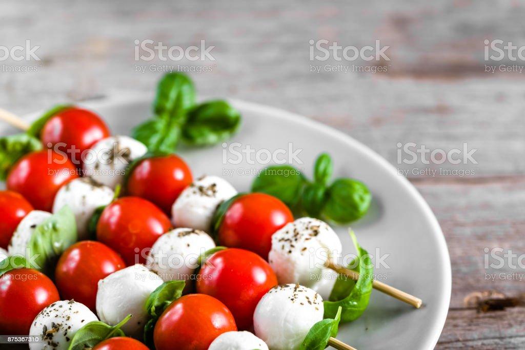 Caprese salade - brochette met tomaat, mozzarella en basilicum, Italiaans eten en gezond vegetarisch dieet concept foto