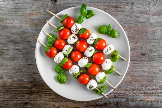 caprese-salat - spieß mit tomate, mozzarella und basilikum, italienisches essen und gesunde vegetarische diät-konzept - caprese salat stock-fotos und bilder