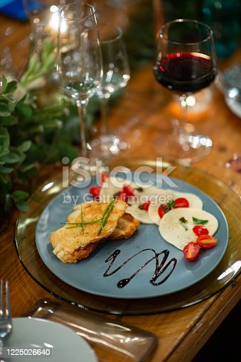 Caprese Salad Starter on a Plate with Red wine in a glass on a table ready to eat.
