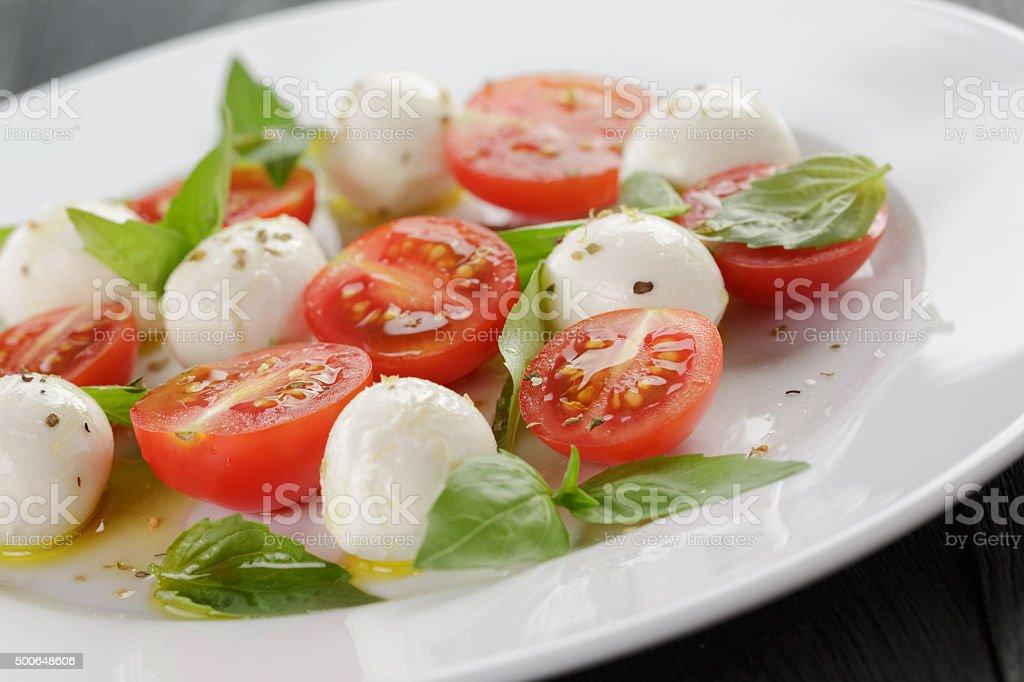 caprese salad with mini mozzarella balls and tomatoes stock photo