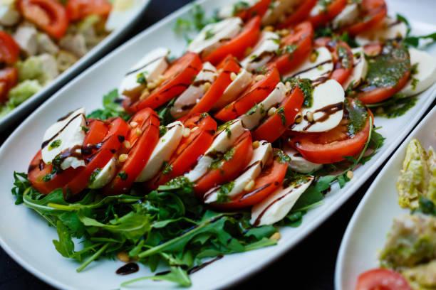 caprese-salat mit mozarella-käse, tomaten und basilikum - caprese salat stock-fotos und bilder