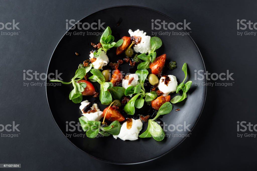 Caprese salad with mozzarella, tomato, basil and balsamic vinegar arranged on black plate and dark background. Top view stock photo