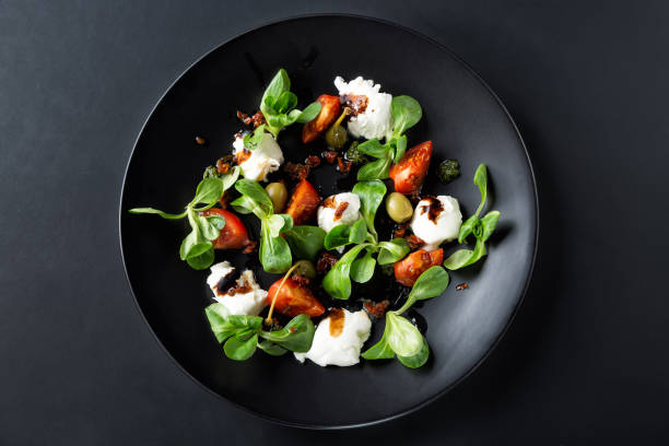 caprese salad with mozzarella, tomato, basil and balsamic vinegar arranged on black plate and dark background. top view - food styling stock photos and pictures