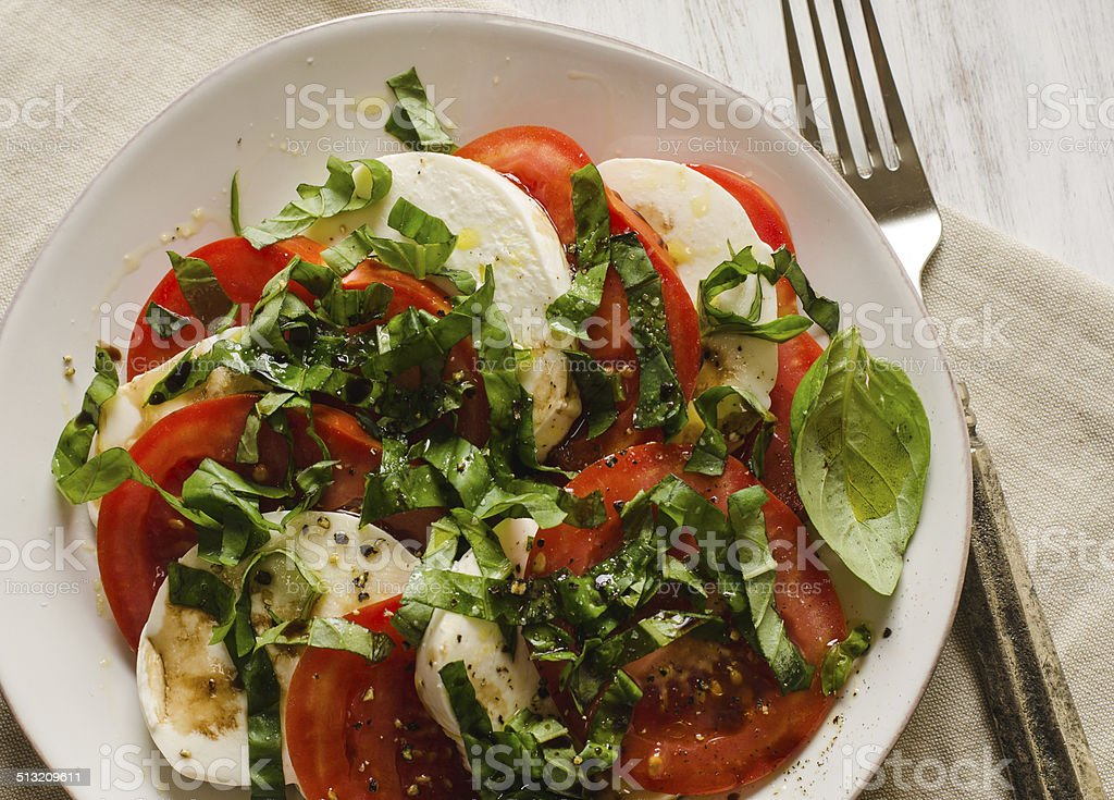 Caprese salad with tomatoes, basil, mozzarella cheese on white plate stock photo