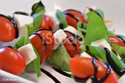 Tomato, basil, fresh mozzarella and balsamic glaze on wooden sticks. Close up of a fresh and healthy appetizer.