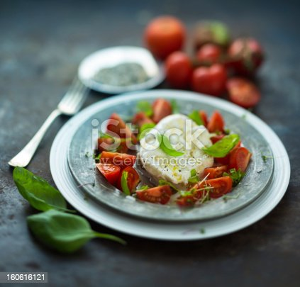 Caprese salad variation -mozzarella bur rata on a metal plate surrounded with tomatoes and asparagus