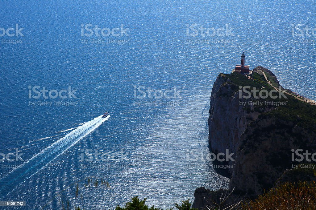Capri above Mediterranean sea, lighthouse and ship crossing water stock photo
