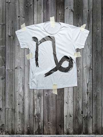 capricorn sign on white t-shirt stuck to gray wood