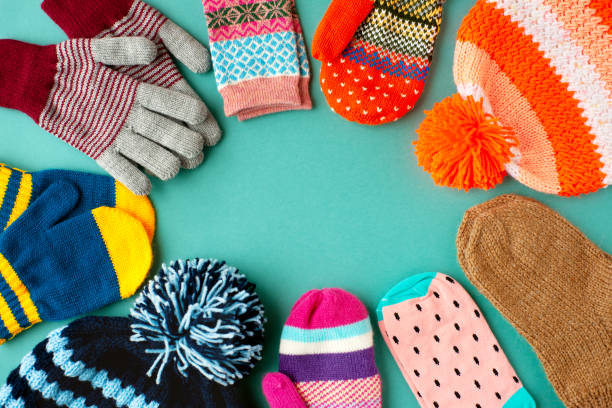 Caps, mittens, gloves and socks are stacked in a circle. View from above. Warm clothes in the form of hats, mittens, gloves and socks for autumn and winter. Warm clothes for cold seasons. warm clothing stock pictures, royalty-free photos & images