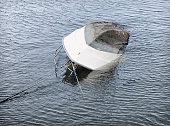 An overturned boat sinking in deep water.