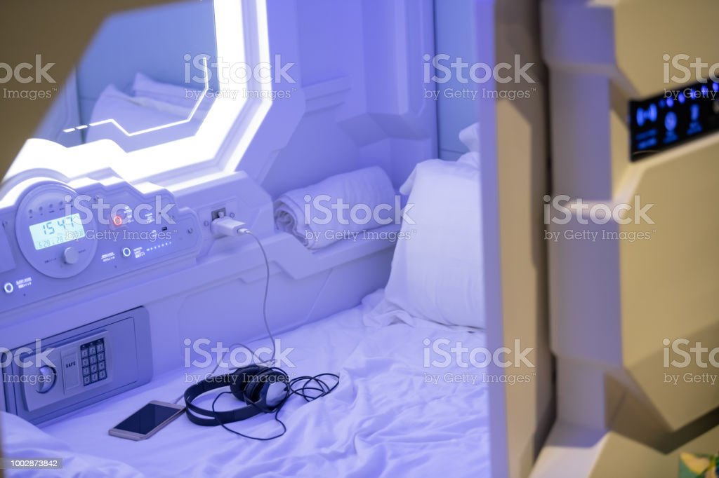 capsule hotel room with phone and headphone set on the bed in malaysia