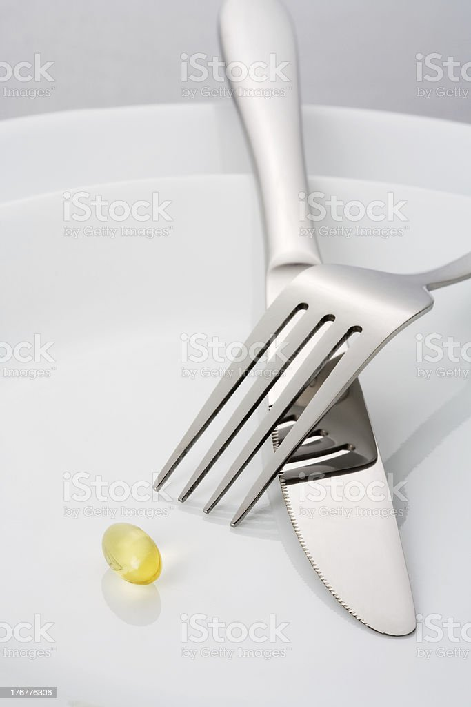 Capsule on plate with fork and knife royalty-free stock photo