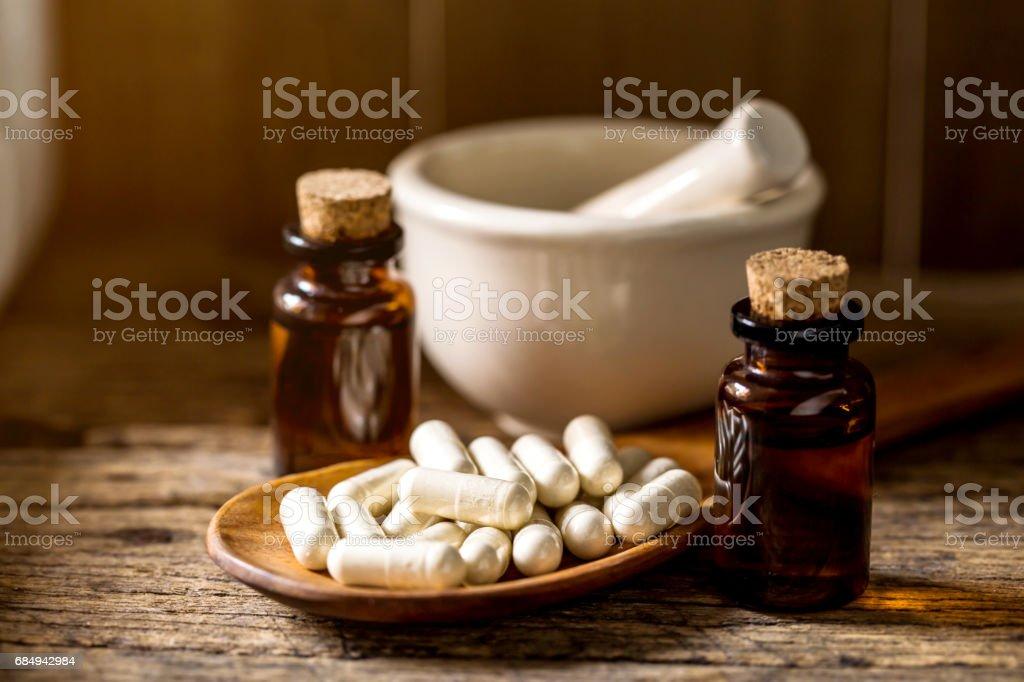 Kapsel Pille mit Kräuter, ätherische Öle und Keramik Mörser auf hölzernen Hintergrund für alternative medizinische Konzept. Lizenzfreies stock-foto