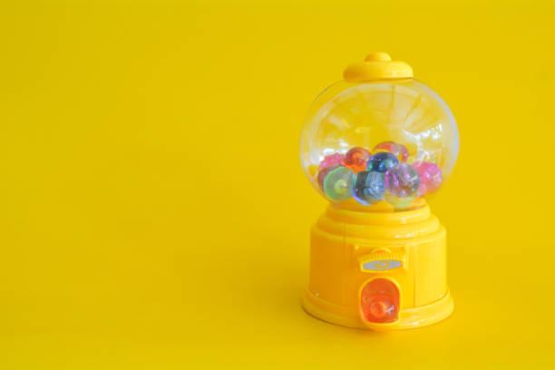 kapsel spielzeug abstrakte minimal gelb hinterlegt - spielesammlung stock-fotos und bilder