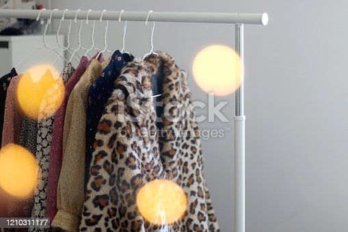 Colorful eccentric wardrobe on a clothing rack. Selective focus, bokeh lights in the foreground.