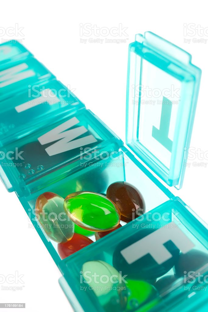 Capsules and a daily medicine pill box. royalty-free stock photo