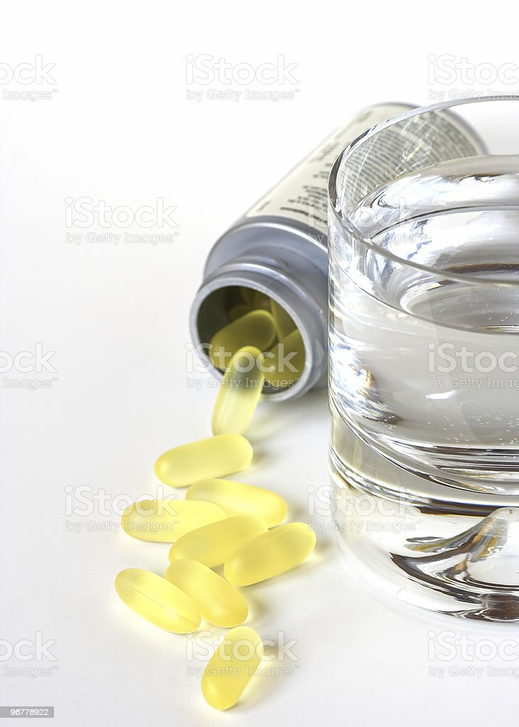 Capsules and a Glass of Water royalty-free stock photo