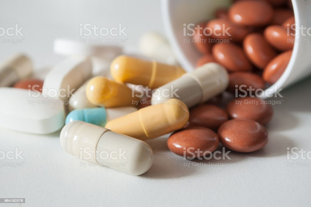capsules and drug tablets falling from bottle on white background royalty-free stock photo