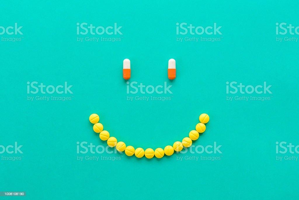 Kapseln und Pillen in Smilng Gesicht angeordnet – Foto