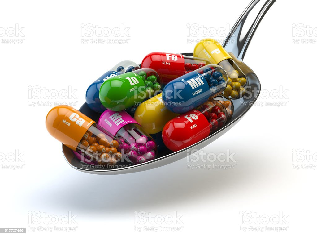 Capsules and pills in spoon, isolated on white. stock photo