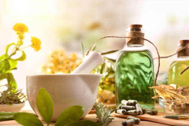 Capsules mortar and essence of plants elaboration concept front detail stock photo