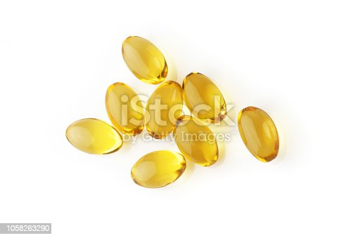 Pile of capsules with cod liver oil close-up isolated on white background. Top view point.