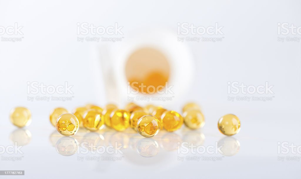 Capsules of fish oil spilled out open container royalty-free stock photo