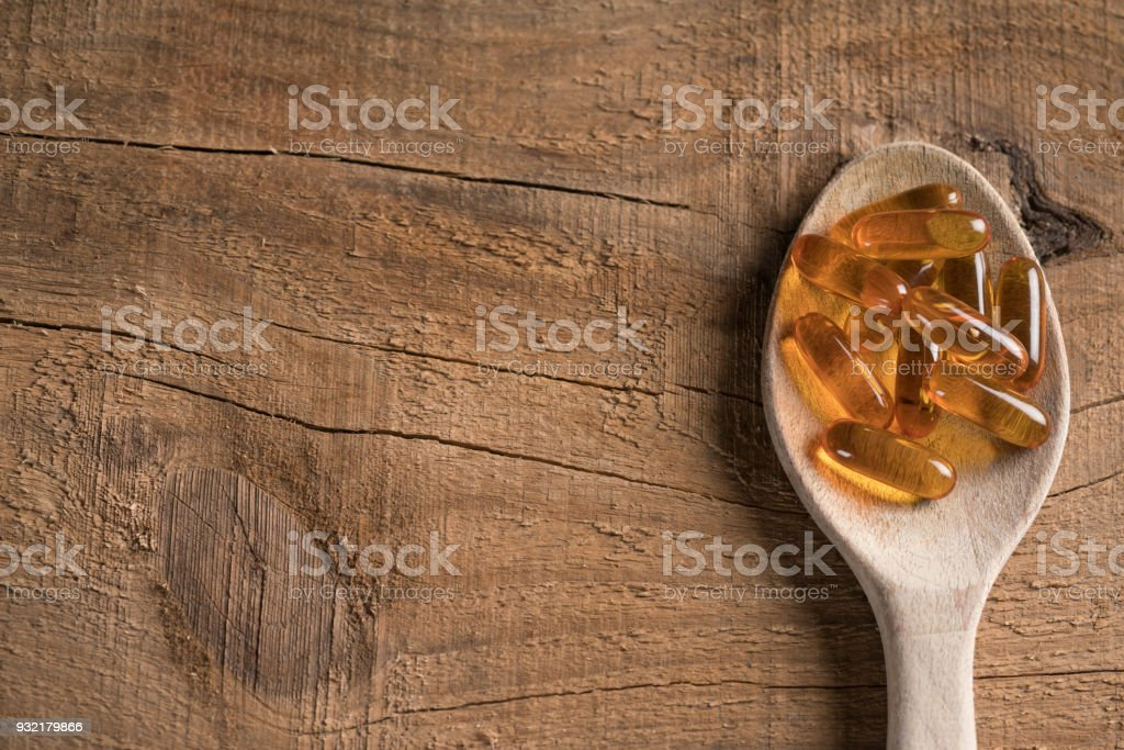Capsules Omega 3  on the wood spoon stock photo