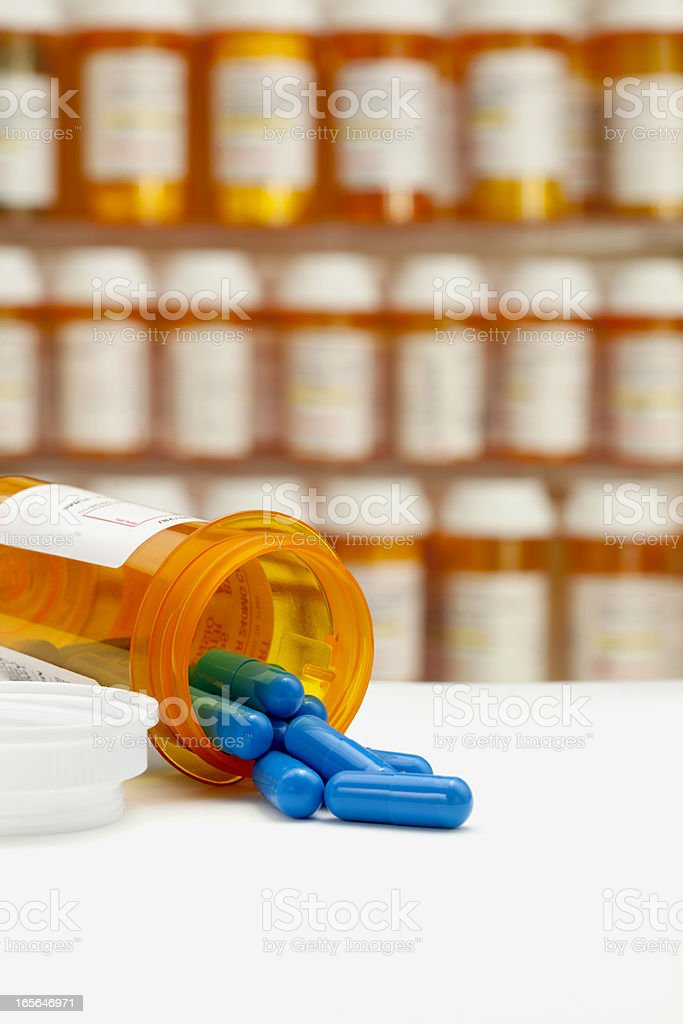 Capsules Spilling from Bottle With Rows of Medicine in Background stock photo
