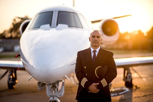 Portrait of a pilot in uniform holding his cap in front of the private jet aeroplane. Sunrise is in the background.