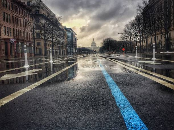 US Captiol from Pennsylvania Avenue In the morning before an Inauguration, Pennsylvania Ave damp with rain shows the blue line of the parade route from the United States Capitol Building, in Washington DC. inauguration stock pictures, royalty-free photos & images