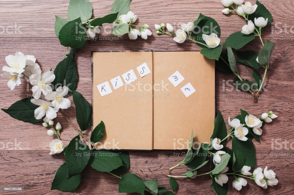 Caption 'Kiss me' writing on a notepad calligraphy. Frame of flowers and jasmine petals on the wooden background. Greeting card. Conceptual photography. Wedding invitation card. Valentine day. Art; royalty-free stock photo