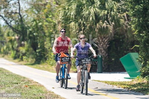 istock Captiva people riding bikes bicycles on trail sidewalk in park by beach and road in Fort Myers, Florida 1073356256