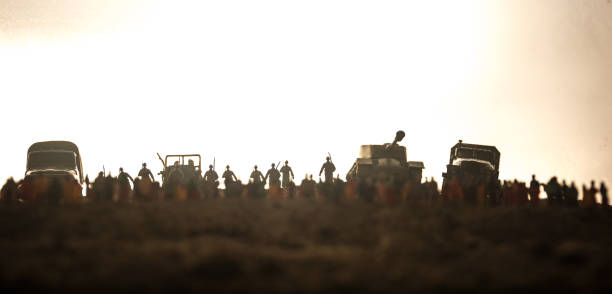 Captured by enemy concept. Military silhouettes and crowd on war fog sky background. World War Soldiers and armored vehicles movement while scared people watching. Artwork decoration. Captured by enemy concept. Military silhouettes and crowd on war fog sky background. World War Soldiers and armored vehicles movement while scared people watching. Artwork decoration. Selective focus mass murder stock pictures, royalty-free photos & images