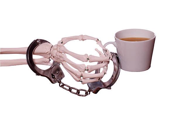captured coffee with handcuff on skeleton hand - coffe with death bildbanksfoton och bilder