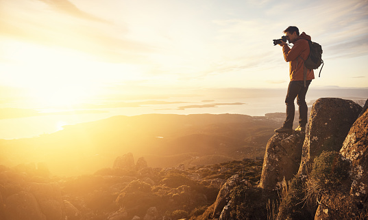 Shot of a young man taking pictures from the top of a mountain