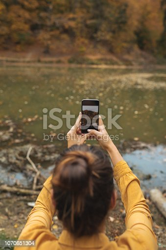 Young woman taking pictures with her cellphone outdoors