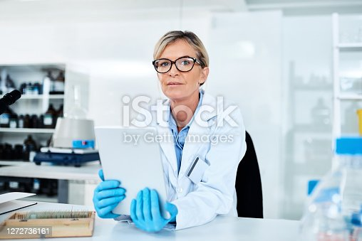 Portrait of a mature scientist using a digital tablet in a lab