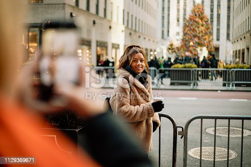 Two women taking photos facing the Rockefeller Christmas Tree in New York City at Christmas time.