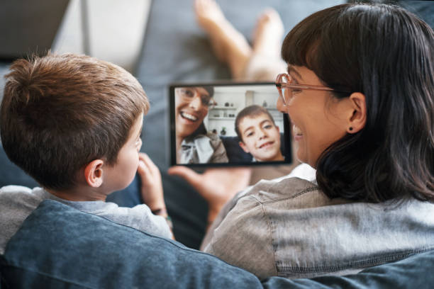 Capturing memories that'll last a lifetime Rearview shot of a mother and her little son using a digital tablet together at home last stock pictures, royalty-free photos & images