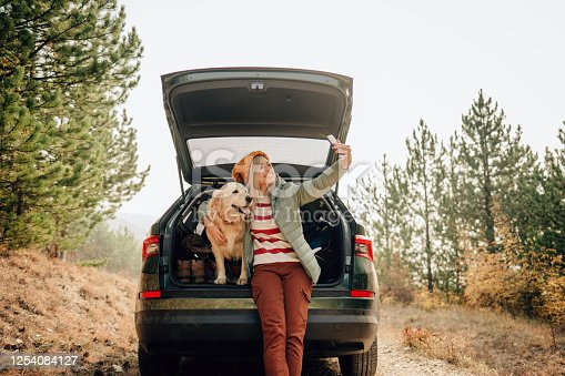 Photo of a young smiling woman and her dog sitting the trunk of a car on a beautiful autumn day; capturing precious moments of their road trip and taking a short break it the middle of a forest.