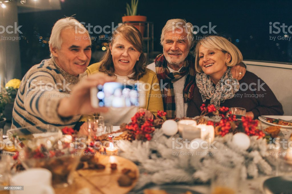 Capturing Thanksgiving memories Photo of a two senior couples, who celebrates Thanksgiving together, capturing their holiday memories with a mobile phone, by making a selfie 60-69 Years Stock Photo